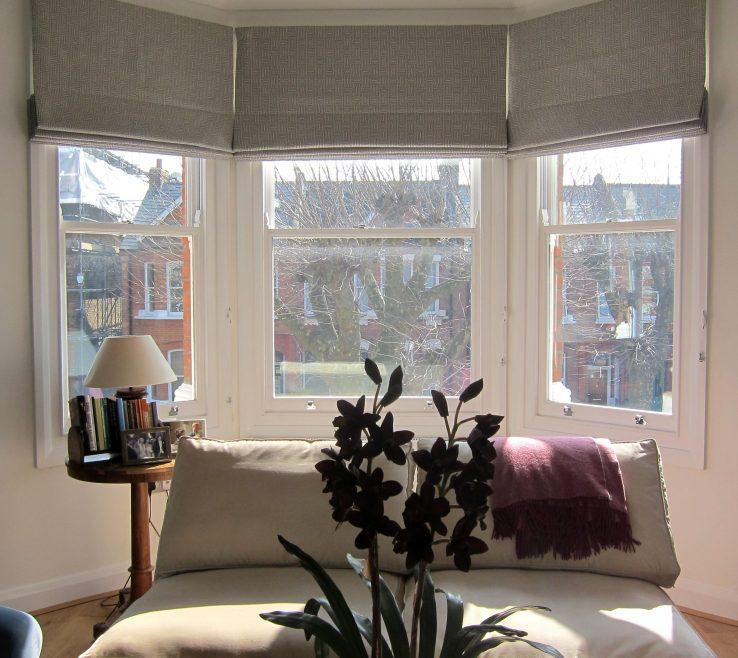 Endearing Bay Window Bedroom Of Geometric Patterned Roman Blinds In A Window.